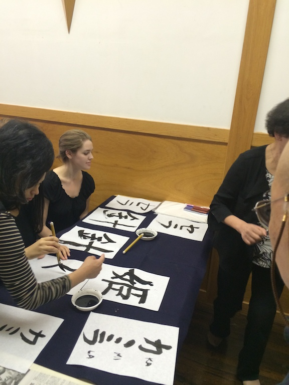 Student looks at her shodo (japanese calligraphy) work during the workshop at the Japanese Culture Center in Chicago.